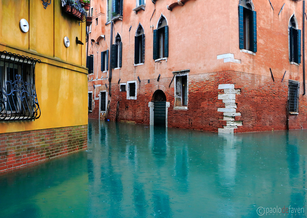 """The junction between Rio di San Provolo and Rio San Severo, two canals in Venice, Italy. Taken on a rainy morning of January, with an exceptional high level of the water due to the """"acqua alta"""" (high tide), the phenomenon that occasionally flood the city of Venice in winter."""