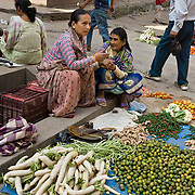 "Two women sell vegetables on the street in Kathmandu (sometimes called ""Kantipur""), the largest city in Nepal (population 700,000). The original inhabitants are Newars, who speak the language Nepal Bhasa. However, Nepali is the lingua franca of the valley and is the most widely spoken language in this country of diverse ethnic groups, who speak somewhere between 24 to 100 different languages and dialects. The city stands at an elevation of 6235 feet / 2230 meters."