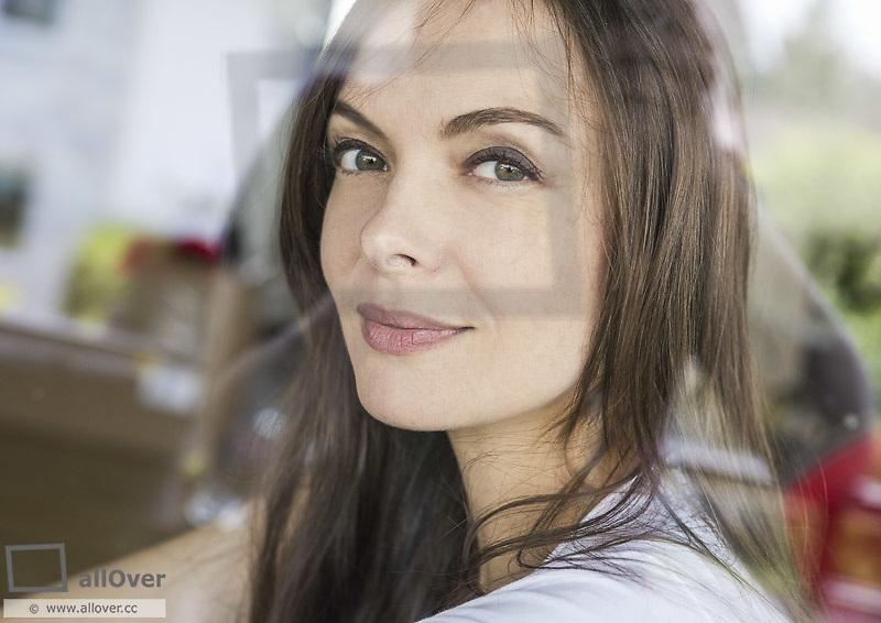 Junge Frau durch Scheibe fotografiert, Portraet (model-released)