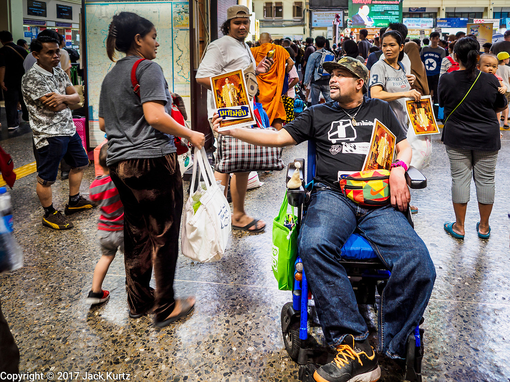 """11 APRIL 2017 - BANGKOK, THAILAND: A man in a wheelchair hands out photos of Bhumibol Adulyadej, the Late King of Thailand, as Songkran holiday travelers walk into Hua Lamphong train station in Bangkok. Songkran is the traditional Thai Lunar New Year. It is celebrated, under different names, in Thailand, Myanmar, Laos, Cambodia and some parts of Vietnam and China. In most places the holiday is marked by water throwing and water fights and it is sometimes called the """"water festival."""" This year's Songkran celebration in Thailand will be more subdued than usual because Thais are still mourning the October 2016 death of their revered Late King, Bhumibol Adulyadej. Songkran is officially a three day holiday, April 13-15, but is frequently celebrated for a full week. Thais start traveling back to their home provinces over the weekend; busses and trains going out of town have been packed.     PHOTO BY JACK KURTZ"""