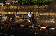 Sri Lankans cross the tracks near the south bound train March 11, 2005 Colombo, Sri Lanka. Train service is returning to a near normal schedule after massive disruptions from the December 26, 2005 tsunami that killed over 40,000 country wide.
