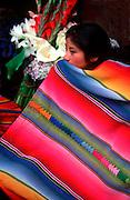 GUATEMALA, HIGHLANDS, MARKETS Chichicastenango; famous Sunday market, Maya Indian woman selling flowers on the steps of Santo Tomas Church