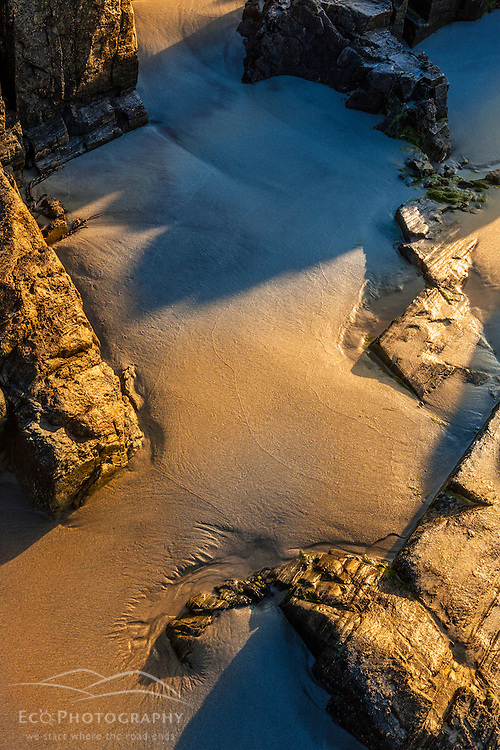 Rocks, sand, and shadows on the beach at Great Island Common in New Castle, New Hampshire.