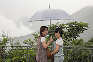 Tourists with umbrellas at The Great Wall of China.