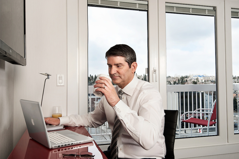 Advertising photography for Hotel Elan. Business man working at an in-suite workstation.