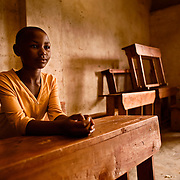 A teenage girl, Adelphine, waits for class to begin in the school of the genocide survivors village of Rugerero Rwanda.