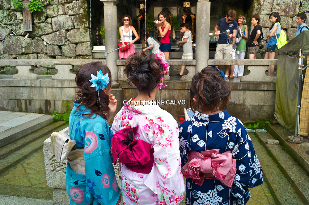 Tourists try to collect falling water from the Otawa-no-taki waterfall with long metal cups at Kiyomizu-dera temple.