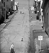 Boys sidewalk sledding on steep San Francisco hill street, 1952