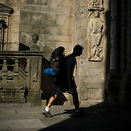 Pilgrim entering the Cathedral. Santiago de Compostela, Galicia . Spain . The WAY OF SAINT JAMES or CAMINO DE SANTIAGO following the French Route, between Saint Jean Pied de Port and Santiago de Compostela in Galicia, SPAIN. Tradition says that the body and head of St. James, after his execution circa. 44 AD, was taken by boat from Jerusalem to Santiago de Compostela. The Cathedral built to keep the remains has long been regarded as important as Rome and Jerusalem in terms of Christian religious significance, a site worthy to be a pilgrimage destination for over a thousand years. In addition to people undertaking a religious pilgrimage, there are many travellers and hikers who nowadays walk the route for non-religious reasons: travel, sport, or simply the challenge of weeks of walking in a foreign land. In Spain there are many different paths to reach Santiago. The three main ones are the French, the Silver and the Coastal or Northern Way. The pilgrimage was named one of UNESCO's World Heritage Sites in 1993. When there is a Holy Compostellan Year (whenever July 25 falls on a Sunday; the next will be 2010) the Galician government's Xacobeo tourism campaign is unleashed once more. Last Compostellan year was 2004 and the number of pilgrims increased to almost 200.000 people.