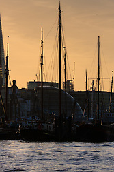 London, March 10th 2015. The sun sets over London after a warm early spring day. PICTURED: Dutch sailing barges tied up at Hermitage Moorings in Wapping.