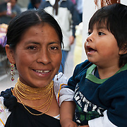 Woman holds boy, wears gold jewelry, in Otavalo, Ecuador, South America. The culturally vibrant town of Otavalo attracts many tourists to a valley of the Imbabura Province of Ecuador, surrounded by the peaks of Imbabura 4,610m, Cotacachi 4,995m, and Mojanda volcanoes. The indigenous Otavaleños are famous for weaving textiles, usually made of wool, which are sold at the famous Saturday market and smaller markets during the rest of the week. The Plaza del Ponchos and many shops tantalize buyers with a wide array of handicrafts. Nearby villages and towns are also famous for particular crafts: Cotacachi, the center of Ecuador's leather industry, is known for its polished calf skins; and San Antonio specializes in wood carving of statues, picture frames and furniture. Otavaliña women traditionally wear distinctive white embroidered blouses, with flared lace sleeves, and black or dark over skirts, with cream or white under skirts. Long hair is tied back with a 3cm band of woven multi colored material, often matching the band which is wound several times around their waists. They usually have many strings of gold beads around their necks, and matching tightly wound long strings of coral beads around each wrist. Men wear white trousers, and dark blue ponchos. Otavalo is also known for its Inca-influenced traditional music (sometimes known as Andean New Age) and musicians who travel around the world.