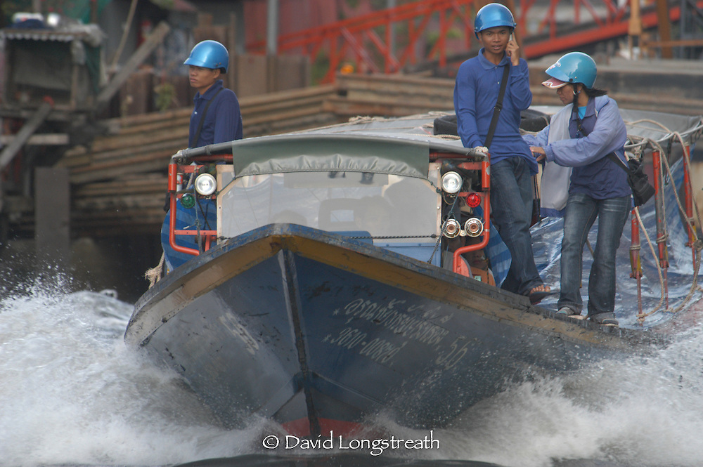 Canal boat workers carry out their duties on boats used as water taxis in downtown Bangkok.