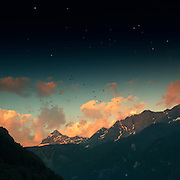 Clouds over a sun illuminated alpine mountain range in Italy - manipulated photograph