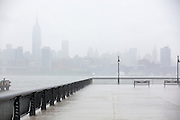 deserted pier in Hoboken, NJ overlooking New York City on a rainy and foggy day.