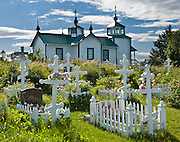 """The Russian Orthodox Church in the town of Ninilchik was redesigned and constructed in 1901 in Alaska, USA. In the graveyard, notice that the Russian Orthodox Cross has two extra arms: the top arm represents the inscribed acronyms [ INRI in Latin,  in Greek, and a Hebrew version, meaning """"Jesus the Nazarene, King of the Jews"""" ], and the angled bottom arm is his footrest. Russian Orthodox religion was born in Kiev in the """"land of the Rus"""" in 988 AD as a branch of Eastern Orthodox Christianity. After Russian discovery of Alaska and the Aleutian Islands in 1741, Russian fur traders taught Christianity to Alaskan Natives. The first eight Russian Orthodox missionaries came to Kodiak Island, Alaska (Russian America) in 1794. The religion spread amongst Alaskans, and the monks mission was made a diocese of the Russian Orthodox Church a few years after the United States purchased Alaska from Russia in 1867. Ninilchik is on the Sterling Highway on the west side of the Kenai Peninsula on the coast of Cook Inlet, 186 miles by road from Anchorage and 38 miles from Homer. The Alaska Native Claims Settlement Act recognized Ninilchik as an Alaska Native village. Ninilchik hosts the annual Kenai Peninsula State Fair."""