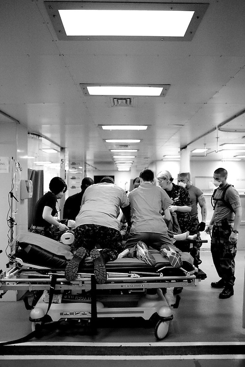 Doctors move a newly-arrived Haitian earthquake victim from a stretcher to a gurney in the casualty receiving area on board the USNS Comfort, a U.S. Naval hospital ship, on January 21, 2010 in Port-au-Prince, Haiti. The Comfort deployed from Baltimore with 550 medical personnel on board to treat victims of Haiti's recent earthquake, and arrived on January 20.