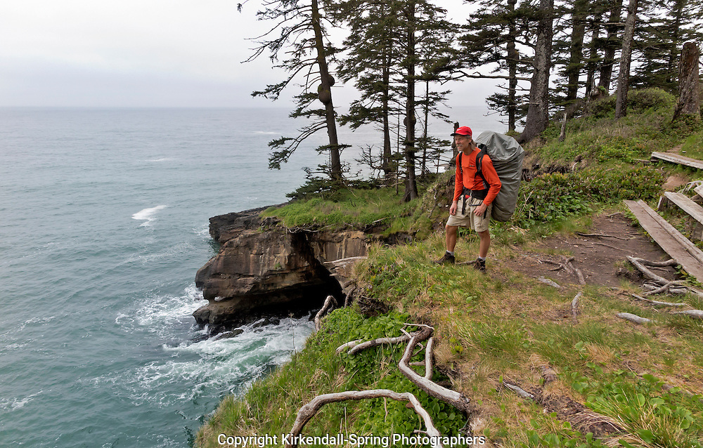BC00473-00...BRITISH COLUMBIA - Hiker pausing at a vista point overlooking the Pacific Ocean north of Tsusiat Falls Campsite on Vancouver Island's West Coast Trail in the Pacific Rim National Park.