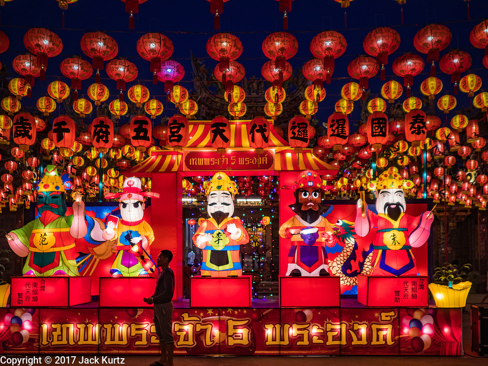 28 JANUARY 2017 - SAMUT PRAKAN, SAMUT PRAKAN, THAILAND: A man looks at the illuminated lanterns at the Chinese New Year Lantern Festival at the Tham Katanyu Foundation shrine in Samut Prakan, a suburb about 15 miles from Bangkok. More than 5,000 handmade lanterns imported from Taiwan are hung on the grounds of the shrine. Some of the lanterns are traditional Chinese lanterns, others are in the shapes of people or deities. There is also traditional Chinese entertainment, likes lion dances, at the festival.      PHOTO BY JACK KURTZ