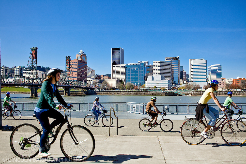 Cyclists bike along the Vera Katz Eastbank Esplanade in Portland, OR. The city skyline and Hawthorne bridge are seen in the background