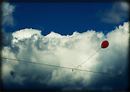 A red balloon stuck on a wire against clouds and blue sky.