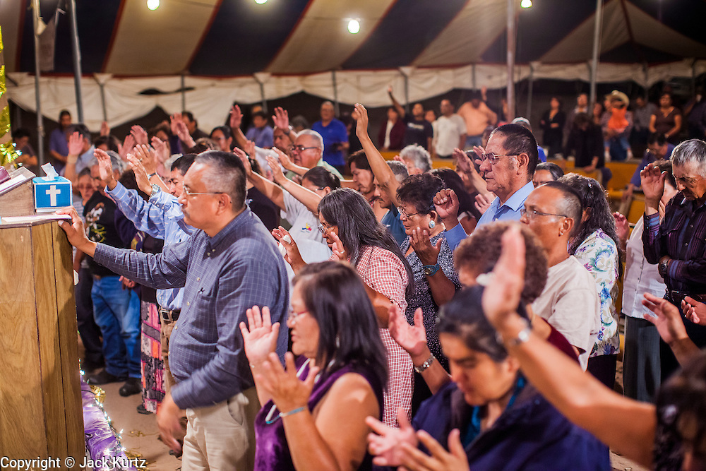 """12 JULY 2012 - FT DEFIANCE, AZ:  People pray during the alter call at the 23rd annual Navajo Nation Camp Meeting in Ft. Defiance, north of Window Rock, AZ, on the Navajo reservation. Preachers from across the Navajo Nation, and the western US, come to Navajo Nation Camp Meeting to preach an evangelical form of Christianity. Evangelical Christians make up a growing part of the reservation - there are now more than a hundred camp meetings and tent revivals on the reservation every year. The camp meeting in Ft. Defiance draws nearly 200 people each night of its six day run. Many of the attendees convert to evangelical Christianity from traditional Navajo beliefs, Catholicism or Mormonism. """"Camp meetings"""" are a form of Protestant Christian religious services originating in Britain and once common in rural parts of the United States. People would travel a great distance to a particular site to camp out, listen to itinerant preachers, and pray. This suited the rural life, before cars and highways were common, because rural areas often lacked traditional churches.    PHOTO BY JACK KURTZ"""