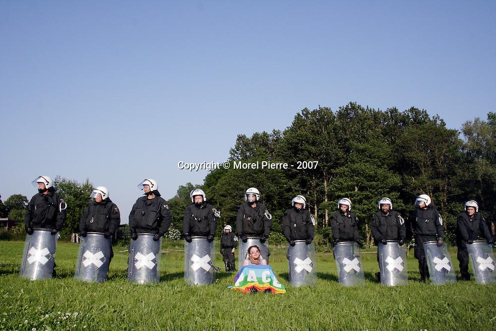 7 Juin - Porte Ouest de la zone rouge : Un manifestant profite du soleil devant une ligne de policiers. Les syndicats de police allemande se sont plaints de journées de travail trop chargées lors du sommet du G8.