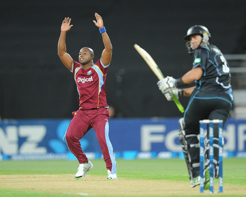 West Indies Tino Best, left, reacts after being hi to the boundary by New Zealand's Ross Taylor in the second T20 International cricket match, Westpac Stadium, Wellington, New Zealand, Wednesday, January 15, 2014. Credit:SNPA / Ross Setford