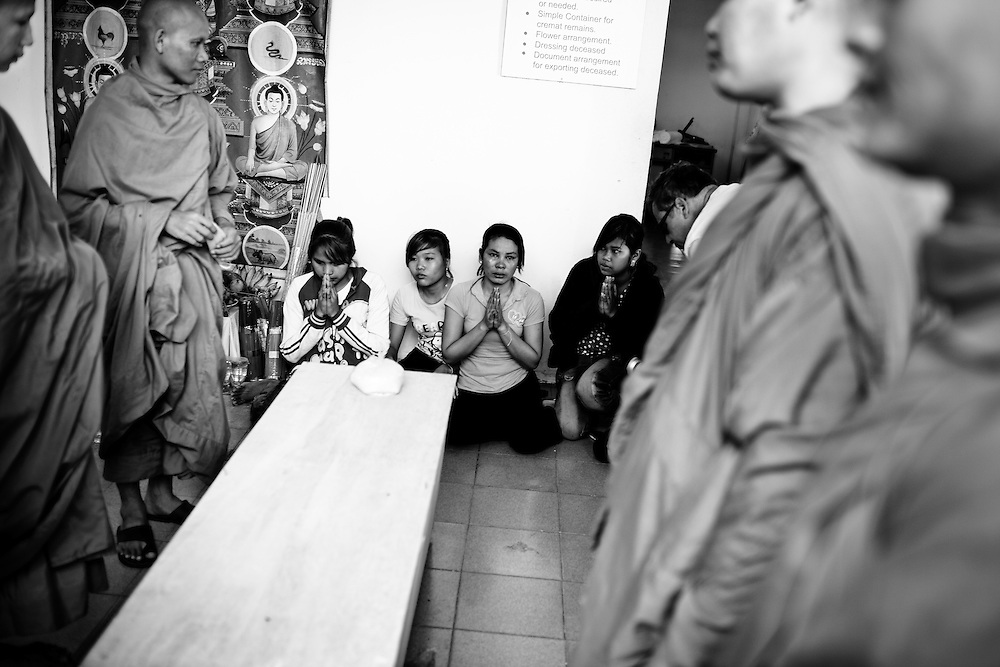 Buddhist Monks pray over the coffin a newly identified victim of the stampede tragedy in Phnom Penh, Cambodia on November 22nd, 2010. Nearly 400 lost their lives when an unknown event caused panic and thousands tried to flee an island over the bridge connecting it to the mainland.
