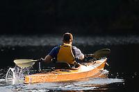 A man paddling a sea kayak accross Otter Lake in the Adirondacks, New York State