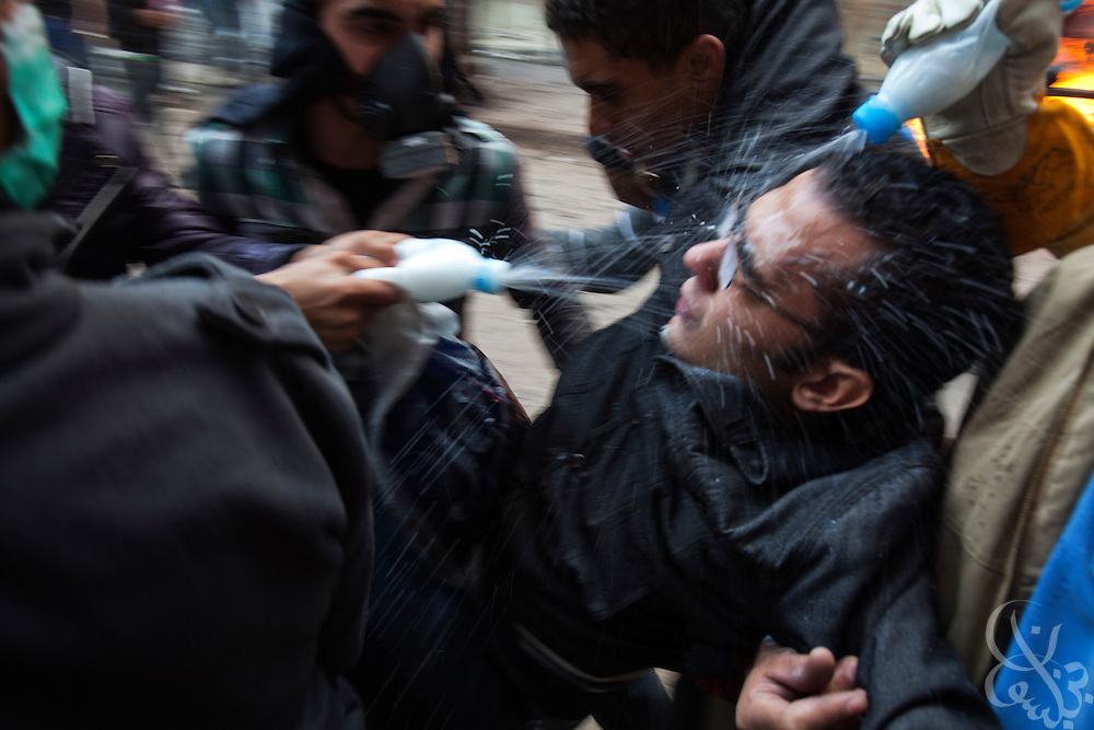 A wounded Egyptian protestor is splashed with a vinegar solution to help negate the effects of tear gas inhalation during clashes with Egyptian security forces November 21, 2011 near Tahrir square  in central Cairo, Egypt. Thousands of protestors demanding the Egyptian military cede power to a civilian authority clashed with Egyptian security forces for a third straight day in Cairo, with hundreds injured and at least 24 protestors killed.  (Photo by Scott Nelson)