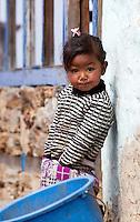 Little Nepali girl standing next to a white wall, Nepal