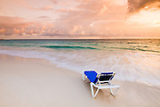 Caribbean, Dominican Republic.  Lounge chair on beach at sunrise in front of all inclusive resort.