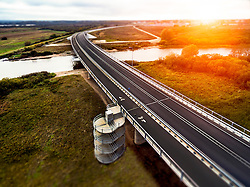 Ihaste bridge over river Emajõgi in Tartu, Estonia. Sunset, sunrise, riverside. Aerial, two lane street, divided road.