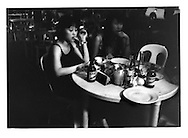 G.R.O. (Guest Relations Officers)  bar girls having a smoke waiting for male customers to arrive at one of Mabini Steet's numerous bar/restaurants that provide very thinly veiled houses of prostitution, Manila, Philippines.