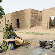 Adama Garba prepares the evening meal at her home in the village of  Nakaidabo in the Tessaoua region of Niger. She has only the beans in her right hand and a pinch of salt to feed her family of seven.