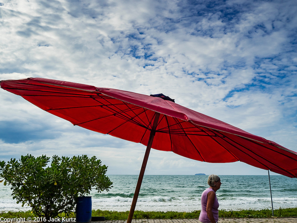 17 JANUARY 2016 - KLEANG, RAYONG, THAILAND:  A European tourist walks past a red beach umbrella at Laem Mae Phim Beach in Rayong province of Thailand.         PHOTO BY JACK KURTZ