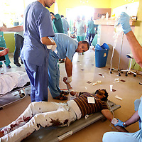 Volunteer medics perform triage on wounded anti-Gaddafi fighters spread out across the floor at a field hospital on the western outskirts of Sirte, Libya. September 2011.