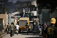During a fierce firefight, Libyan rebels  attack Bab Al Azizyia,  Gadhafi's headquarters compound in Tripoli. After a Caterpillar opened a breach in the outer wall it went around to ram the main gate, as the rebels swarm the compound. 23 August 2011.