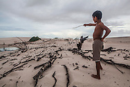Adriel Brito, 13, points to the place where once was the house of his uncle. After he lost the house for the dunes he decided to move to the nearby city of Santo Amaro. During the summer, the lack of water and the strong winds make the dunes advance and take over parts of the oasis. But not only their life is threaten by the tourism and the sand. The Brazilian Institute of the Environment and Natural Resources (IBAMA) is planning to remove them since they live in a National Park. The residents refuse to move since many of them were born there and lived all their lives in the Queimada. They claim that more than a threat they are a protection to the Lençois do Maranhão.