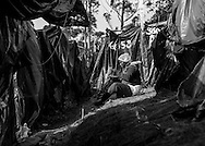 A woman eats between the shacks made of wooden sticks and black plastic bags on the Copa do Povo (People's Cup) camp, Itaquare, São Paulo. The Copa do Povo Camp, is just a few miles from the Arena Corinthians and has 5,000 homeless workers and their families occupied area of fifteen acres. They are homeless after rents skyrocketed because of the World Cup. (Eduardo Leal).