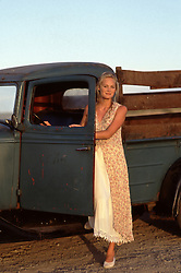 woman standing by an antique truck