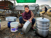04 MARCH 2017 - KATHMANDU, NEPAL: A woman from rural Nepal cleans the pans she uses to make steamed momos (a type of Nepalese dumpling) in an IDP camp in the center of Kathmandu. She lives in the camp with her husband and son and sells momos on the streets of Kathmandu. The camp opened days after the April 2015 earthquake devastated Nepal, killing almost 9,000 people. At its peak, about 1,800 families lived in the camp. The camp is still open nearly two years after the earthquake, about 400 families currently live in the camp. Camp residents say the Kathmandu municipal government is trying to close the camp and is encouraging residents to find new housing. They said the government is cutting off services to the camp and last week stopped the free distribution of water, although water can be purchased for delivery. Most of the people in the camp came to Kathmandu from rural villages in the mountains in the weeks after the earthquake. Many of the residents of the camp, technically homeless, have found work in Kathmandu's bustling construction industry, rebuilding homes destroyed in the earthquake.       PHOTO BY JACK KURTZ