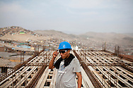 A construction worker builds a school on Tuesday, Apr. 14, 2009 in Ventanilla, Peru.