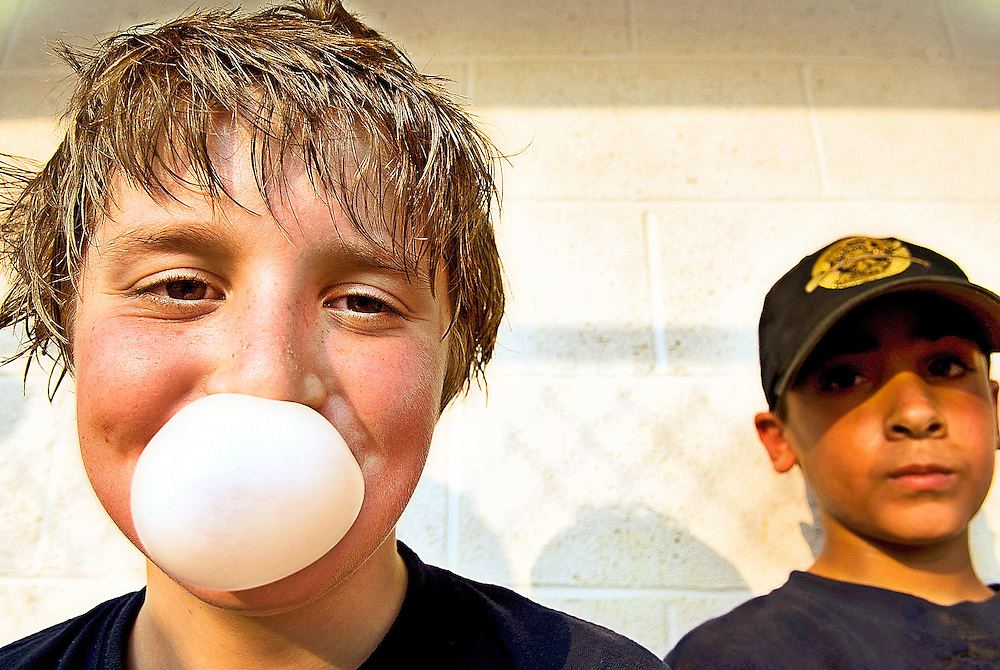 (staff photo by Matt Roth)..Riverdog John Aliprando blows a bubble while Matthew Aubin, right, looks on. The Bats took on the Riverdogs at the Kiwanis-Wallas Park Thursday July 20th, 2006 during a neck-to-neck game, ending in a 16-15 Riverdog win.