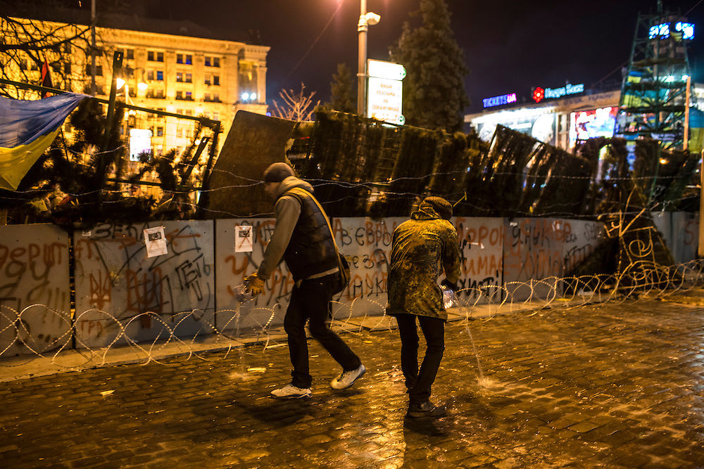 KIEV, UKRAINE - DECEMBER 3: Protesters pour water, which a cold December night will soon turn to ice, in front of a barricade during ongoing anti-government protests in Independence Square on December 3, 2013 in Kiev, Ukraine. Thousands of people have been protesting against the government since a decision by Ukrainian president Viktor Yanukovych to suspend a trade and partnership agreement with the European Union in favor of incentives from Russia. (Photo by Brendan Hoffman/Getty Images) *** Local Caption ***