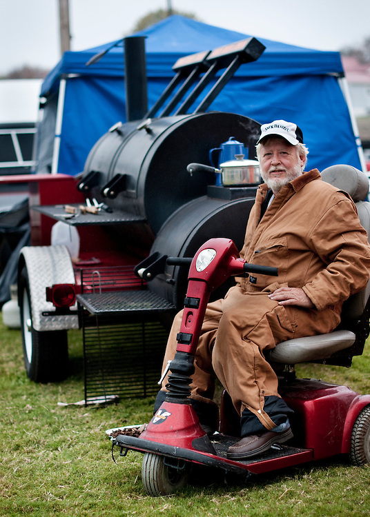 """Michael Ray Reeves Sr, Wild Boars Barbecue..Michael is a forklift dealer from Lynchburg. He had to sell his motorcycles after an accident, and decided to buy a custom built barbecue pit instead. """"They gave me a 75 year warranty"""" he laughs. He's competing in the amateur competition called the Shade Tree Cookoff at the Jack Daniel's Invitational Barbecue 2012....Jack Daniels Invitational Barbecue 2012 - The Jack. .Photographer: Chris Maluszynski /MOMENT"""