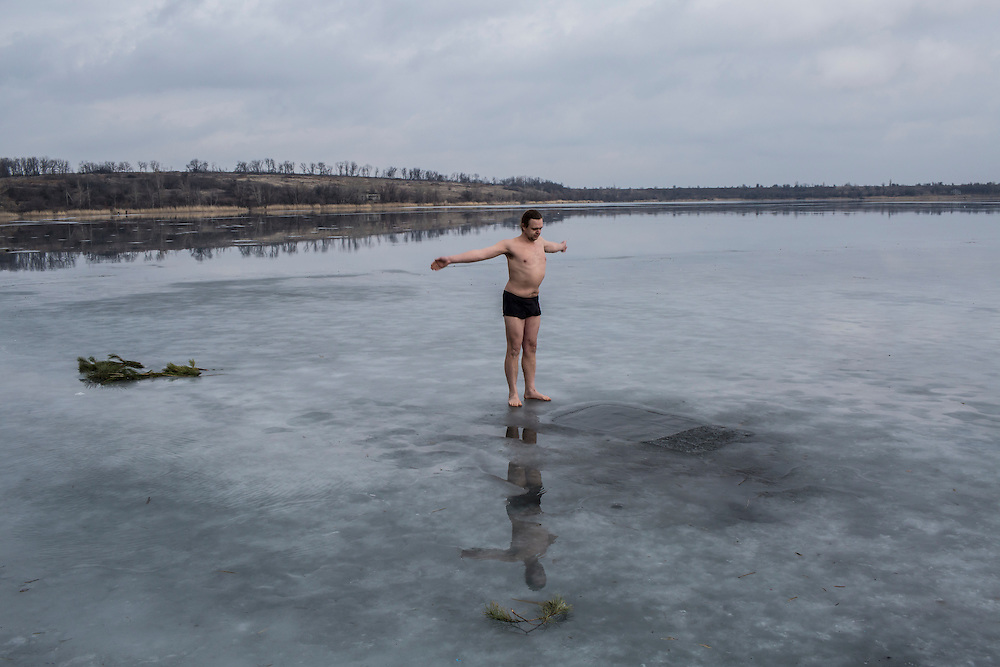 Sergei Korotun warms up before partaking in his daily health ritual of bathing in the icy local reservoir on Sunday, February 14, 2016 in Karlivka, Ukraine.