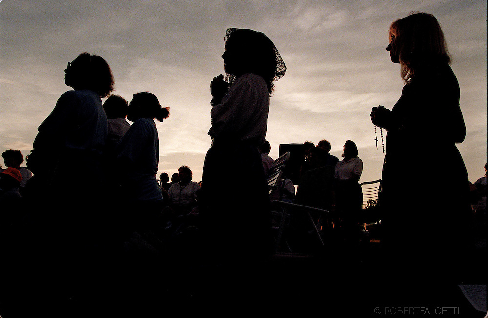 DADE CITY, FLORIDA: Women kneel in prayer at around 6:00 p.m. at the home of Vimer Nagun, a teenager who claimed to have apparitions of the Virgin Mary. Large gold circles and rings were reported in the sky by pilgrims each evening around 6:00 p.m.  (Photo by Robert Falcetti). .