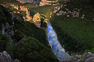 "A view at sunset of the Ardeche river and its gorges, which are actually a wonderful canyon - 35 kms long and 250 meters deep - the river dug for million years in a limestone plateau.  This part of the gorges is placed at about half lenght of the canyon and its main feature is the rock formation visible on the left of the river, know as ""La Cathédrale"" for its vertical, sharp ""spires"". Just to give a sense of scale of this scene, the Cathedral is about 80 meters tall, and I took this picture from a natural balcony at about 200 mts above the river bed. The slice of sky reflected in the river is so sharp and striking, that it almost looks like a rift in the Earth that let one look out to the other side of the planet. Here's where the title come from.  This is a stitch of four verticals."