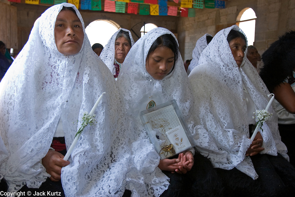 "25 APRIL 2005 - SAN CRISTOBAL DE LAS CASAS, CHIAPAS, MEXICO: First communion mass in the Chamulan Indian community of Yaaltsunum near San Cristobal de las Casas. The Catholic Church in the Chiapas highlands is facing a threat from evangelical Protestant churches, which are experiencing explosive growth, and from ""traditionalist"" Catholic churches, which are not affiliated with the San Cristobal diocese and are controlled by local politicians and powerful indigenous leaders affiliated with the politicians. The traditionalists burn down churches and chapels affiliated with the diocese, threaten the priests and put indigenous men who worship with the diocese in jail.  PHOTO BY JACK KURTZ"